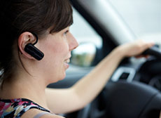 Woman using Bluetooth device headset whilst driving