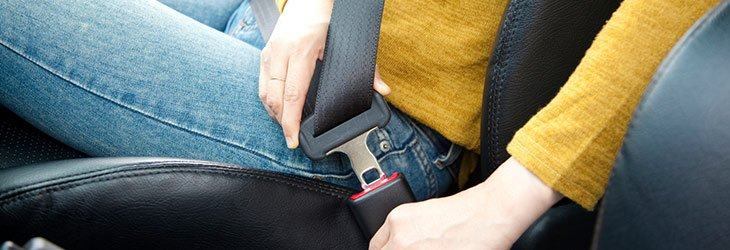 Woman in blue jeans putting her seatbelt on