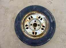 car tyre with rust on in the middle of a desert