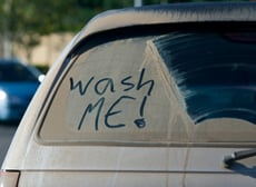 car that is in need of a wash with writing on it