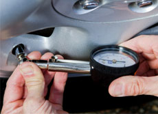 person using an air pressure guage to measure PSI on a tyre