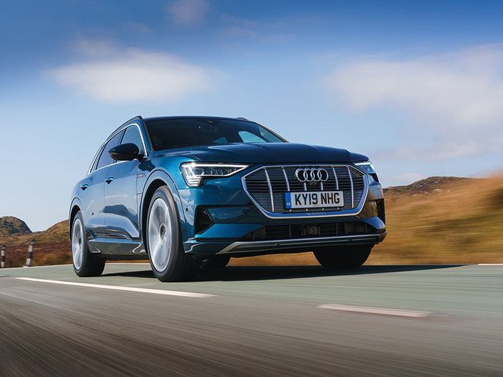 blue audi e-tron electric car driving on road