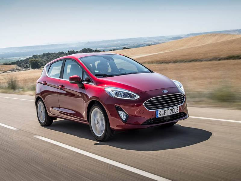 red ford fiesta driving on country road