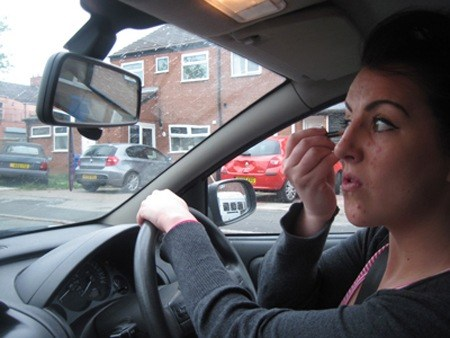 Girl putting make-up on whilst driving (posed)