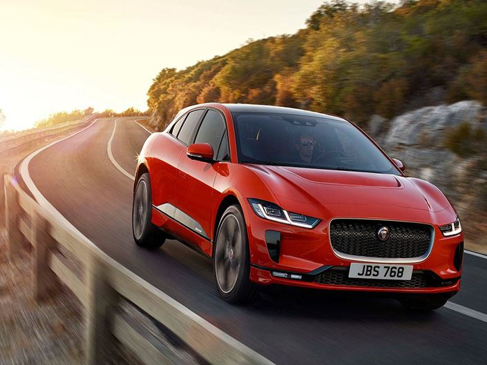 red jaguar i-pace electric car driving on italian road