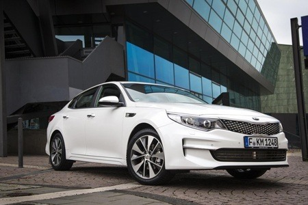 KIA Optima emerges from a buiding car park
