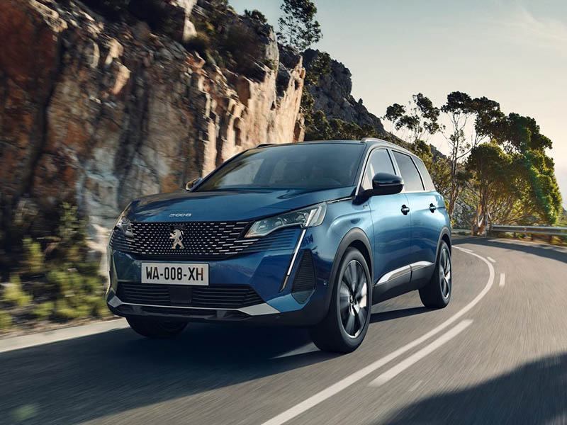 blue peugeot 5008 driving on mountain roads