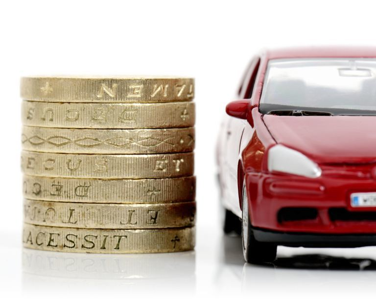 Pound coins next to car