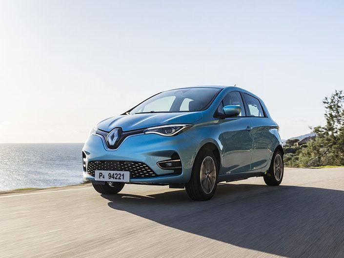 blue renault zoe electric car driving by the sea
