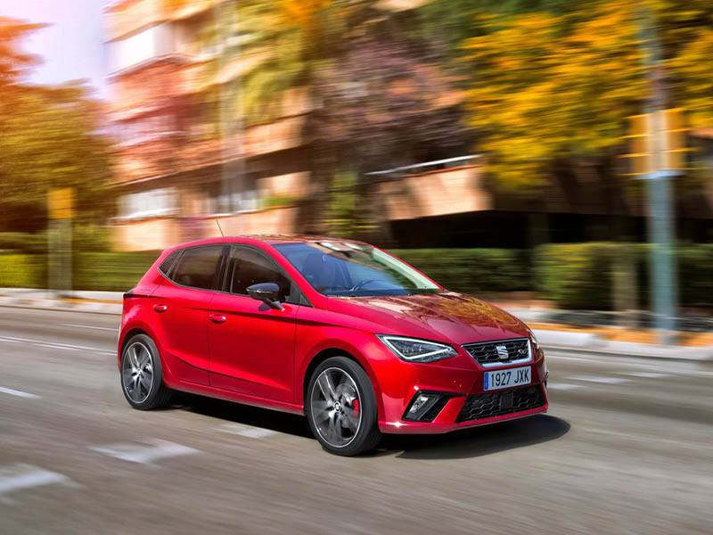red seat ibiza hatchback driving on road