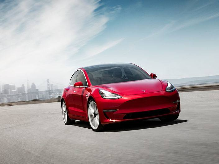 red tesla model 3 driving on road
