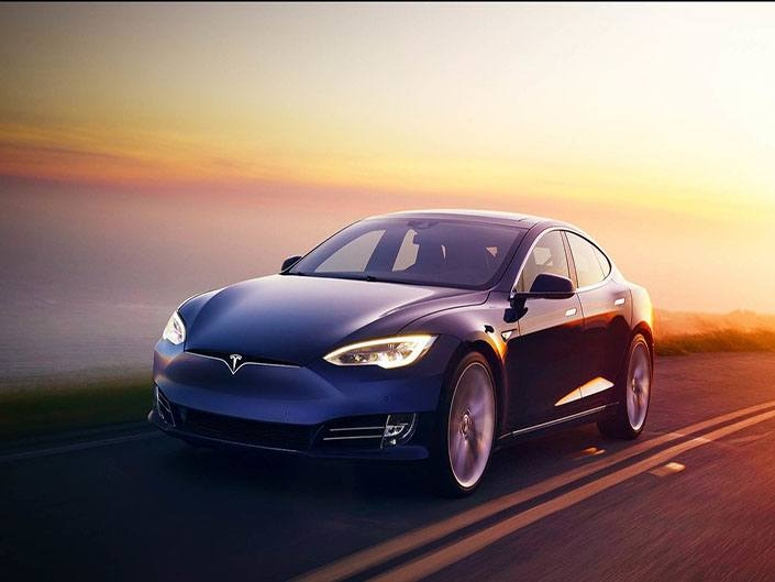 blue tesla model s driving in sunset