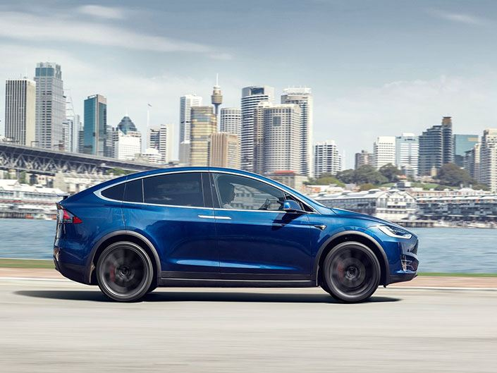 blue tesla model x driving in the city