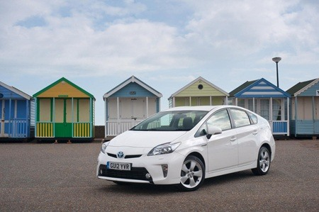Toyota Prius next to some beach huts