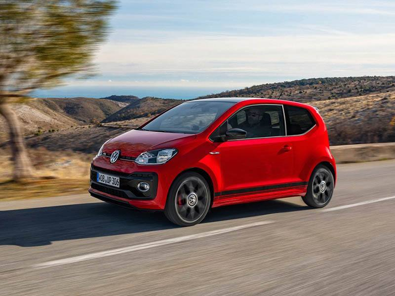 red volkswagen up driving on mountain road