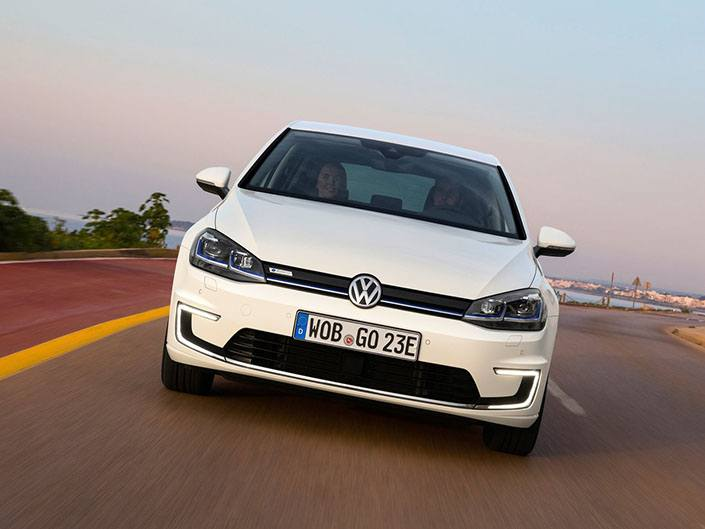 white volkswagen e-golf electric car driving on road