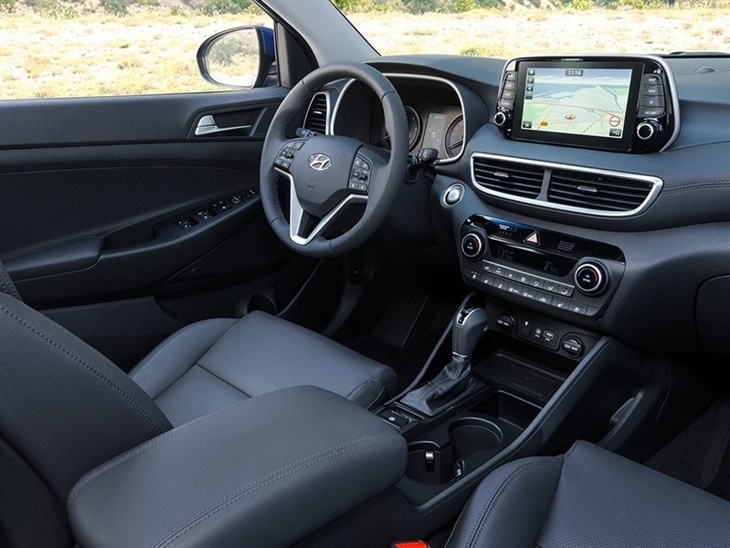 The front interior of a Hyundai Tucson, showing the navigation system and steering wheel