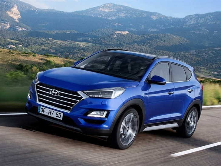 The front Exterior View of A Blue Hyundai Tucson Driving on a road