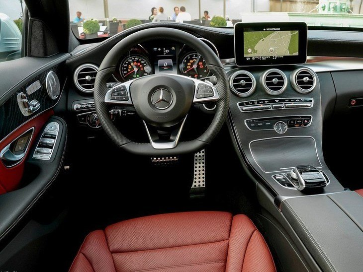 The Interior of a Mercedes Benz C Class Estate showing the Steering Wheel and Navigation
