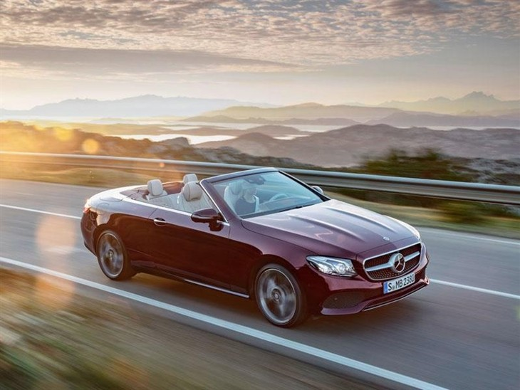 A Side View of the Mercedes Benz E Class Cabriolet with the Top Down in Red Driving