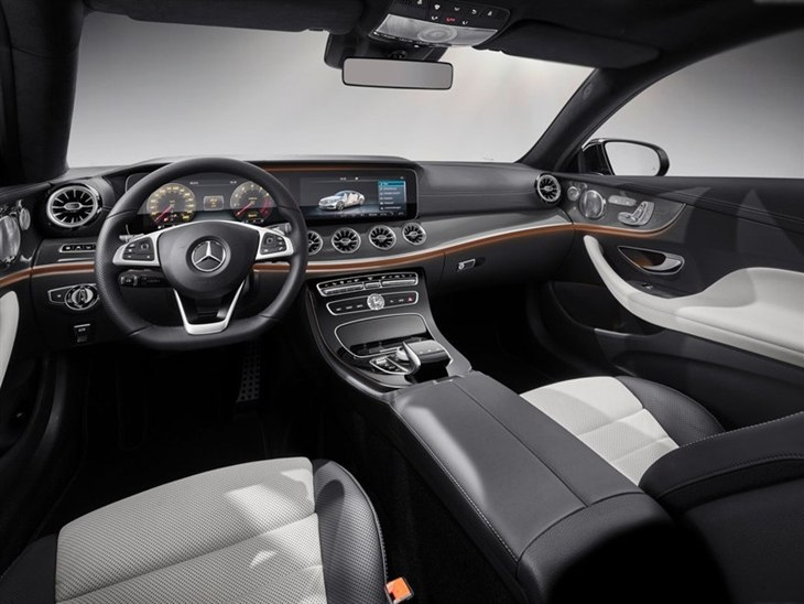 The Interior of a Mercedes-Benz E Class Coupe Showing the Steering Wheel and Center Console