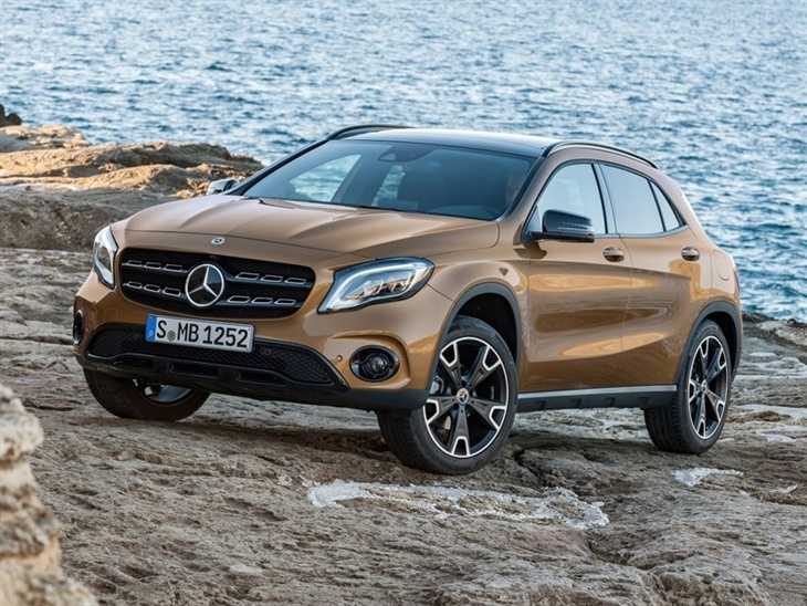 The Front View of a Gold Mercedes Benz GLA on a Cliff