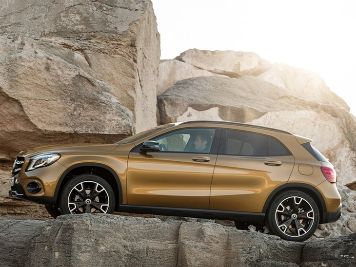 The Side View of a Gold Mercedes Benz GLA on a Cliff