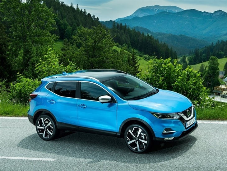 The front exterior view of a blue Nissan Qashqai with mountains in the background