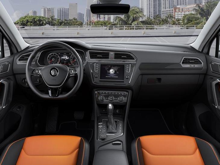An Interior View of a Volkswagen Tiguan showing the Stearing Wheel and Navigation System