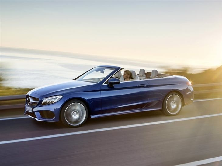 The side of a Mercedes Benz C-Class Cabriolet with the Roof Down in Blue Driving